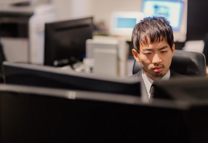 パソコンの前でモニタリング男性のイメージ写真