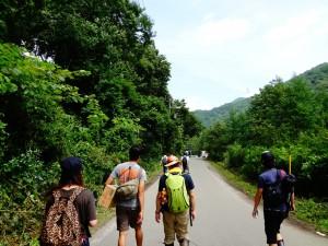バックパックを背負って歩く複数の男女の写真