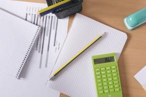 机の上に広がる電卓と文具の写真