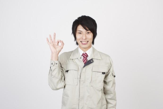 OKサインを出す作業着の男性の写真