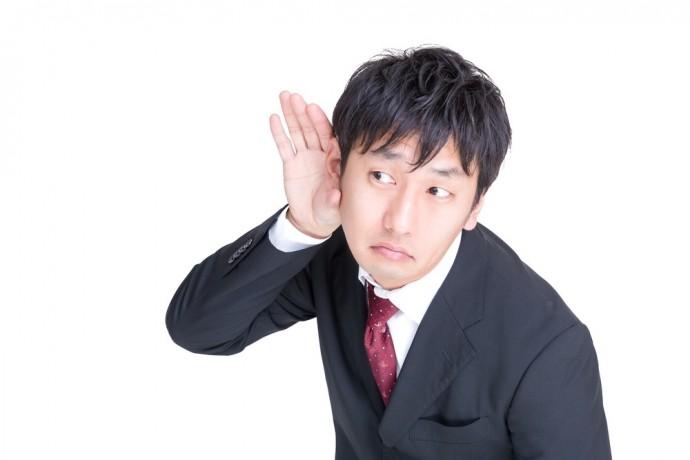 右耳に手を当てている男性の写真